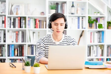 Smart asian young male student study something during internet online courses with laptop computer at home