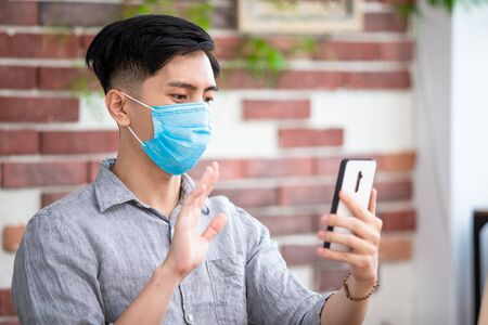 asian man is self quarantine - he use smartphone to video chat with friend at home