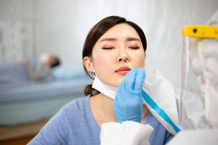 Test de coronavirus - Un travailleur médical prélève un écouvillon pour un échantillon de virus corona d'une femme potentiellement infectée avec la blouse d'isolement ou des combinaisons de protection et des masques chirurgicaux