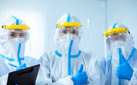 health workers look to you with thumb up gesture - they wear the isolation gown or protective suits and surgical face masks in the control area to prevent the spread of coronavirus