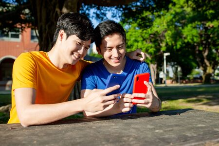 happy young asian teenagers share an interesting APP on smartphone and they feel very happy