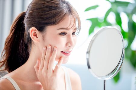 close up of young asian has good skin care and she look in mirror Standard-Bild
