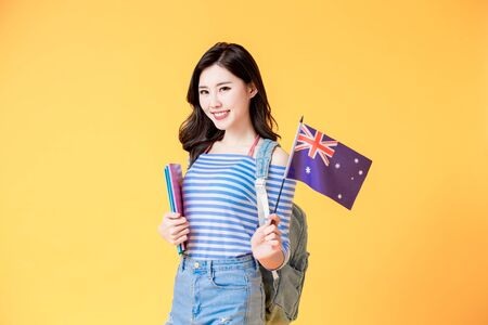 asian female student smile and look to you with Australian flag isolated yellow background
