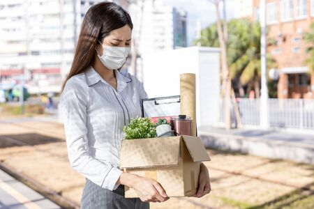 Asian woman being fired because of economic downturn due to coronavirus spread all over the world and she wear face mask on the road