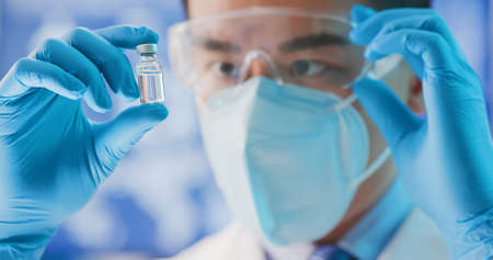 close up of microbiologist or medical worker look to medicine capsule in the laboratory