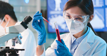 asian microbiologist biotechnology researcher or medical worker look result of blood test with microscope in the lab