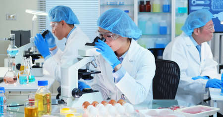 Asian Quality control expert inspecting at food specimen meat in the laboratory