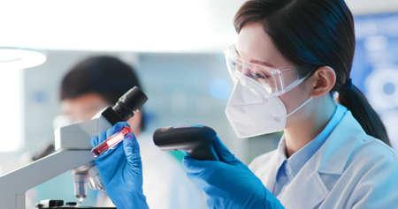 close up of microbiologist or medical worker scan blood test result