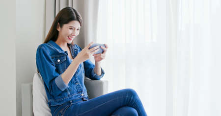 asian woman play game with smart phone and exciting