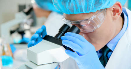 close up of asian scientist team has researching and look microscope in the laboratory Stock Photo