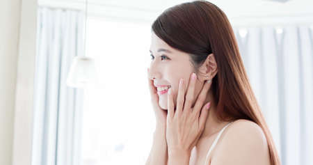 beauty asian girl touch her good skin on face and look mirror at home Stock Photo