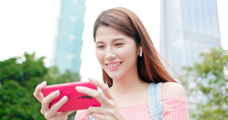asian woman use earbuds playing mobile game with 5g smartphone outdoor-location taipei and taiwan Stock Photo