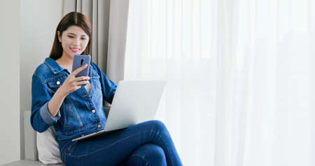 asian woman look smartphone and use laptop to work at home
