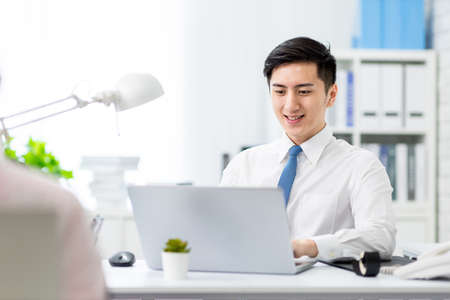 asian young businessman work with laptop in the office