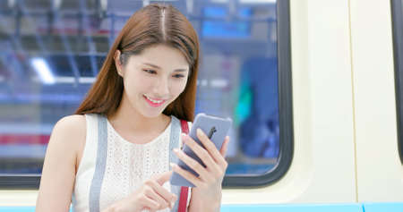 asian young woman use 5g smartphone in the metro train-location taipei and taiwan