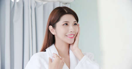 beauty asian girl touch her good skin on face and look mirror in the bathroom Stock Photo