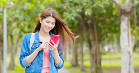 asian woman use smartphone outdoor while walking in the park