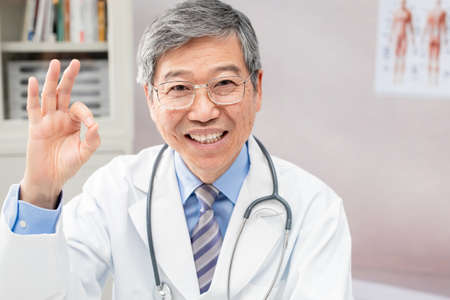 asian male senior doctor smile to you with ok gesture