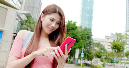 asian woman use 5g smart phone outdoor when traveling-location taipei and taiwan