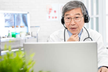 Telemedicine concept-asian senior male doctor talking sore throat symptom to patient on the internet and make a discussion in clinic