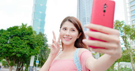 asian woman use 5g smart phone to take selfie outdoor when traveling-location taipei and taiwan Stock Photo
