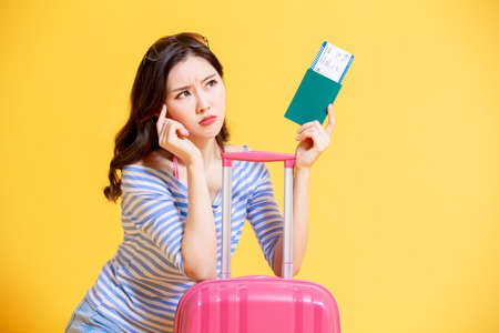 travel woman is upset in front of the yellow background