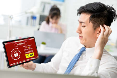 asian worried young businessman looking at tablet pc with ransomware attack words on the screen in office