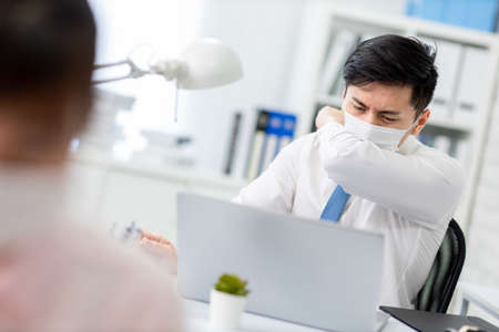 asian young businessman is sick and cough in the office Stock Photo