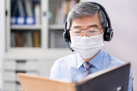 asian senior businessman with face mask join a video meeting with computer microphone headsets in the office