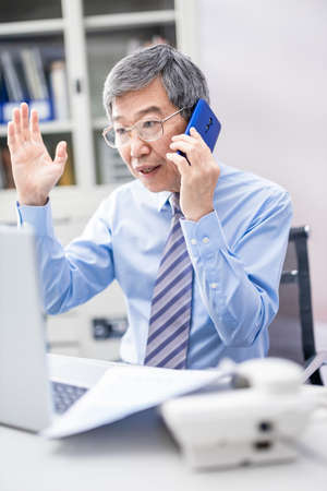 asian senior business man speak on smartphone to discuss his work plan in the office