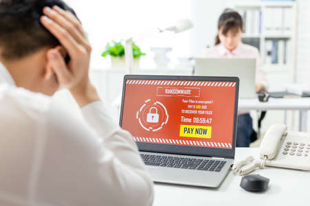 asian worried young businessman looking at laptop computer with ransomware attack words on the screen in office Stock Photo