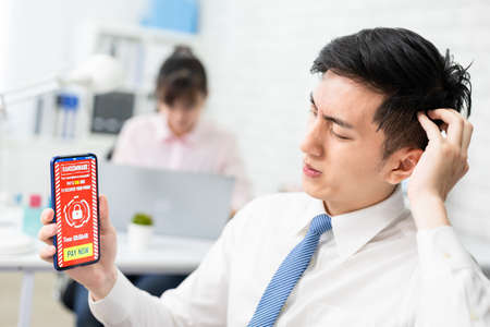 asian worried young businessman looking at smart phone with ransomware attack words on the screen in office