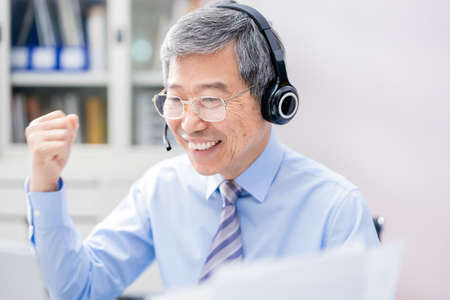 telework concept-Asian senior businessman is very happy to get the order on a video meeting in the office