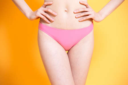 close up of asian woman with laser hair removal bikini line concept on the yellow background
