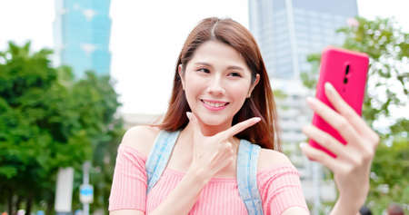 asian woman use 5g smart phone and take selfie outdoor when traveling-location taipei and taiwan