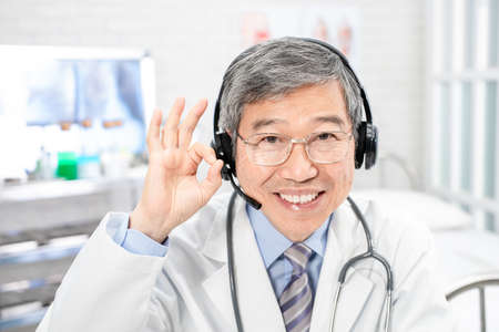 Telemedicine concept-asian senior male senior doctor talking symptom to patient on the internet and make a discussion with ok gesture in hospital Stock Photo