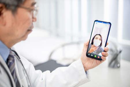 Telemedicine concept-asian senior male doctor explain to the patient about the disease by video chat on cell phone in hospital Stock Photo