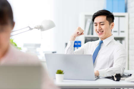 Asian young businessman is very happy with fist gesture in office