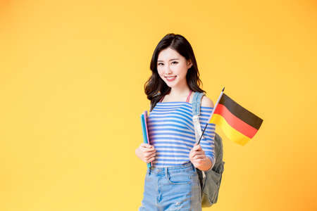 asian female student smile and look to you with germany flag isolated yellow background