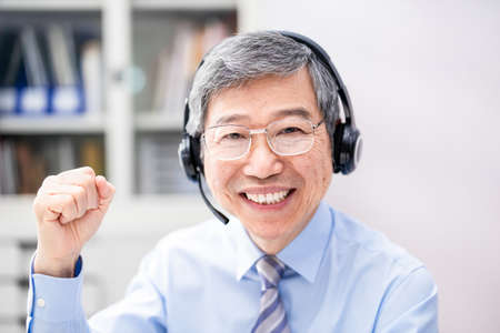 telework concept-Asian senior businessman is very happy and look to webcam on a video meeting in the office