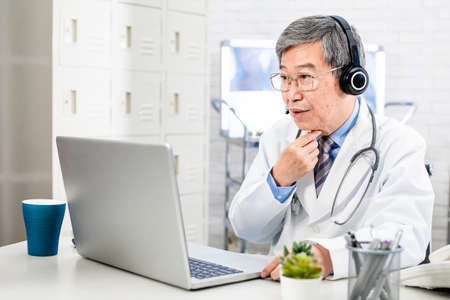 Telemedicine concept-asian senior male doctor talking sore throat symptom to patient on the internet and make a discussion in hospital
