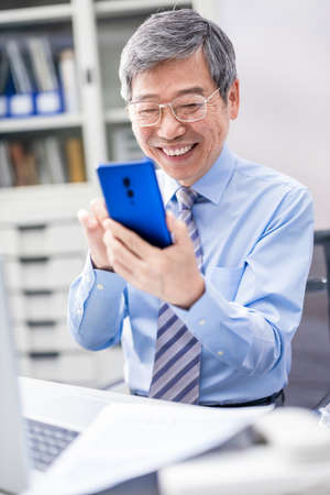 asian elder businessman use smartphone happily in the office Stock Photo