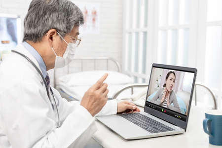 Online Tele medicine concept-asian senior male doctor with face mask has video chat to patient by laptop in hospital