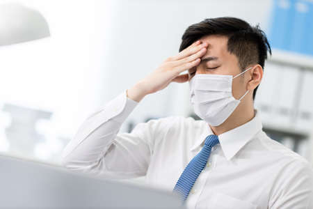 asian young businessman has fever and feel uncomfortable in the office