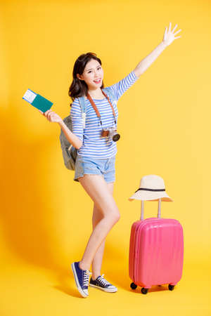 travel woman smile happily with suitcase and passport standing in front of the yellow background