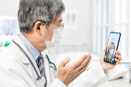 Tele medicine concept-asian senior male doctor with face mask explain to the patient about the disease by video chat on cell phone in hospital Stock Photo