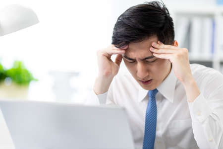 asian young businessman has headache and feel upset in office
