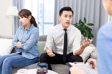 Young unhappy asian couple having marriage counseling and the husband is complaining