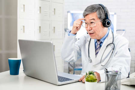 Telemedicine concept-asian senior male doctor talking to patient on the internet and make a discussion in hospital Stock Photo