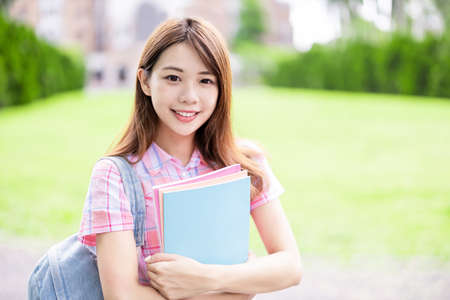 Asian college student smile to you with books holding in hands on campus Stock Photo